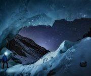 Un observador de estrellas contempla la constelación de la Osa Mayor perfectamente alineada con la ventana de la entrada a una gran cueva de glaciares en Engadin, Suiza.