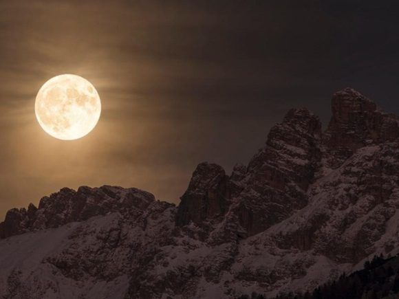 En esta imagen contemplamos una magnífica vista de la superluna iluminando el cielo nocturno, detrás de la montaña Marmarole, en el corazón de la cadena montañosa de los Dolomitas en Italia.