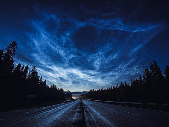 Espectacular instantánea en la que vemos nubes noctilucentes que se extienden a través del cielo iluminando el paseo de un motociclista a casa en esta dramática escena.