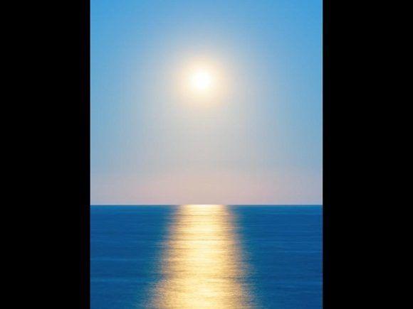 Una foto inesperada de la Luna que se levanta sobre el reluciente océano de la costa de Wairarapa, que la hacen tener una semejanza notable con el sol.