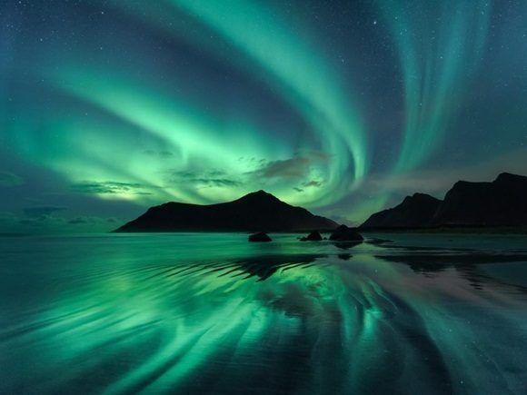 El reflejo de los giros verde brillante de la Aurora boreal se ve reflejado en las ondulaciones de la playa de Skagsanden.