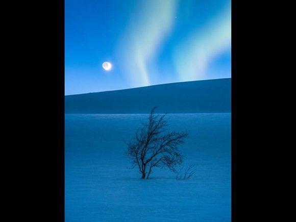 En la imagen contemplamos la luna creciente y la mirada de Marte sobre Saltfjellet en Noruega mientras las luces del norte parecen emanar del paisaje nevoso.