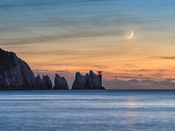 Estamos ante una luna creciente (7%) fija en el cielo de la tarde sobre las agujas del faro en la extremidad occidental de la isla de Wight (Inglaterra).