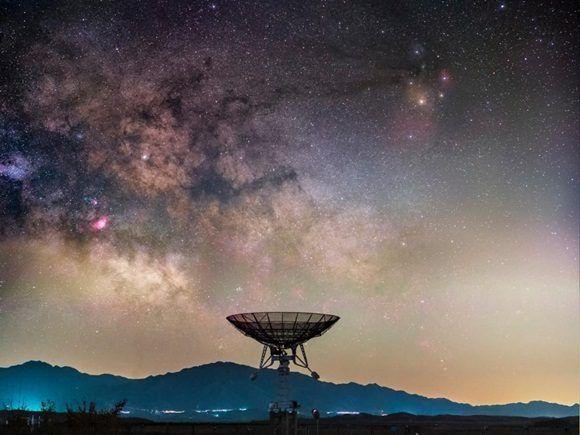 La Vía Láctea se eleva por encima de un pequeño radiotelescopio en la Estación Miyun, el Observatorio Astronómico Nacional de China, en los suburbios de Beijing.