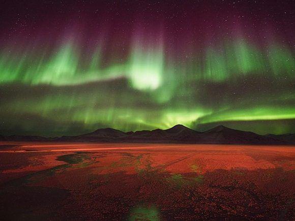 Los colores púrpura y verde de las auroras boreales irradian sobre la ciudad minera de carbón de Svea, en el archipiélago de Svalbard, en el océano glacial ártico.