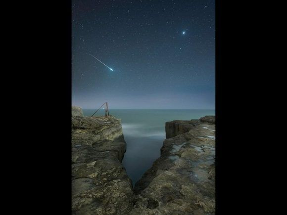 Una estrella fugaz destella a través del cielo sobre el paisaje escarpado de Portland, Dorset. La imagen es producto de dos exposiciones: una para el cielo y otra para las rocas.
