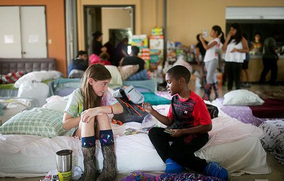 Una voluntaria de 8 años, Elizabeth Hill, juega con un evacuado, Skyler Smith. Foto: AP.