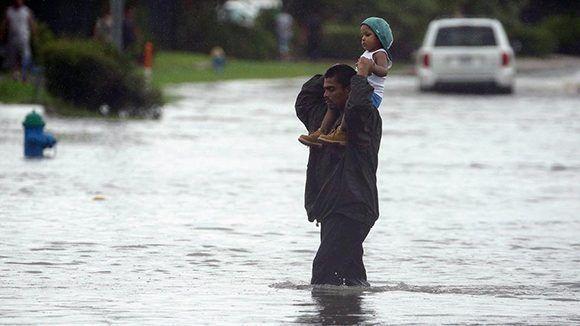 Un hombre carga a su hijo para salvarlo de las inundaciones en el noroeste de Texas. Foto. Charlie Riedel/ AP.