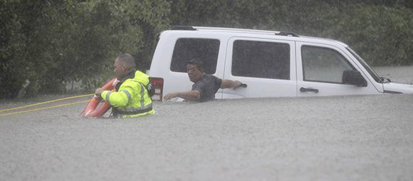 Un agente del sheriff rescata a un hombre de su coche en Houston, el domingo. Foto: AP.