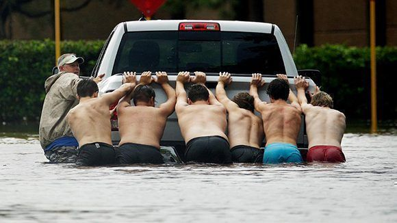 Siete hombres empujan una camioneta en Houston. Foto: Charlie Riede/ AP.