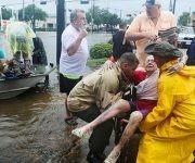 Unos vecinos usan su bote personal para rescatar a una señora llamada  Jane Rhodes en Friendswood, Texas. Foto: Steve Gonzales/ Houston Chronicle.