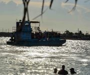 Embarcación a su paso por la playa La Boca, al atardecer, en el municipio norteño de Puerto Padre, en Las Tunas, Cuba. Foto: ACN/ Yaciel Peña.