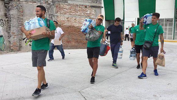 Los jugadores de Zacatepec ayudan a remover escombros. Foto: A. González / El País