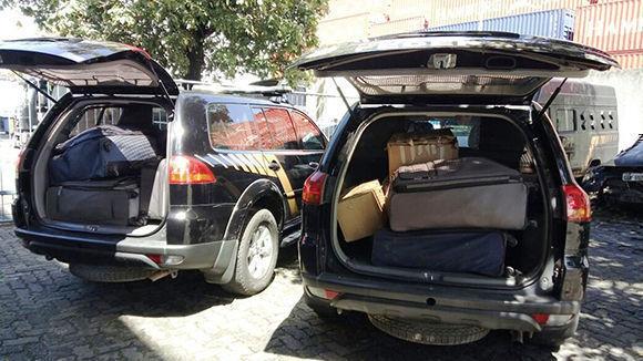 Los coches de la policía brasileña llevan cajas y maletas repletas de dinero encontrados a un banco donde serán contabilizados y depositados en una cuenta judicial. Foto: Hispantv.
