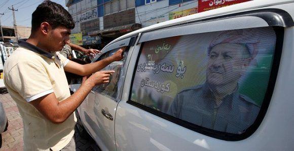 Un hombre decora su coche con propaganda en favor del referéndum de independencia del Kurdistán. Foto: Reuters.