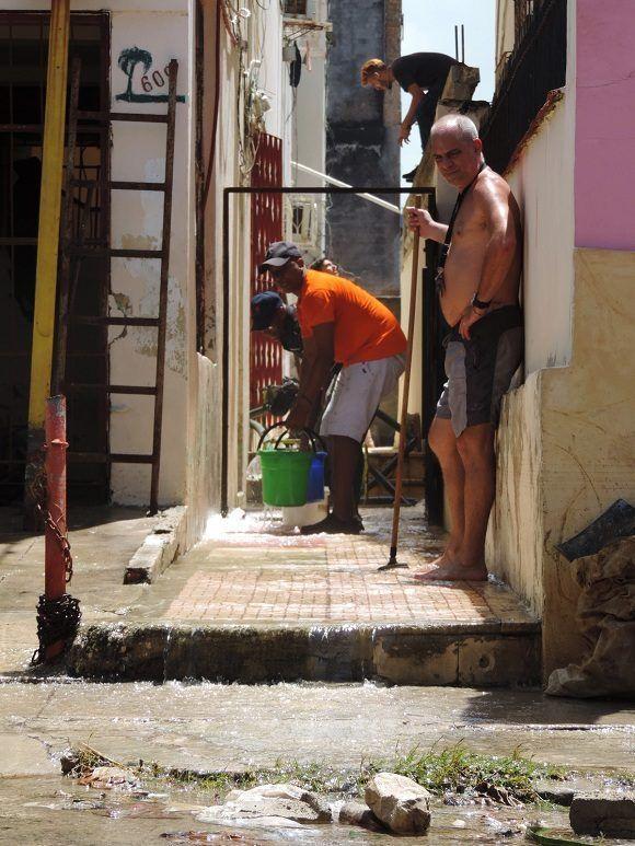 El trabajo colaborativo entre vecinos, aunque más lento, también ha sido una vía efectiva para extraer agua de viviendas inundadas. Foto: Darío Gabriel Sánchez García/CUBADEBATE.