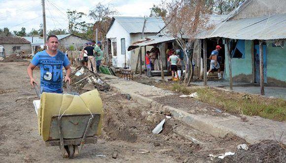 Un poblador traslada un colchón expuesto al sol, en Palmarito, comunidad más afectada por el huracán Irma en el poblado de Júcaro, del municipio Venezuela, como parte de la recuperación en Ciego de Ávila. Foto: Osvaldo Gutiérrez / ACN