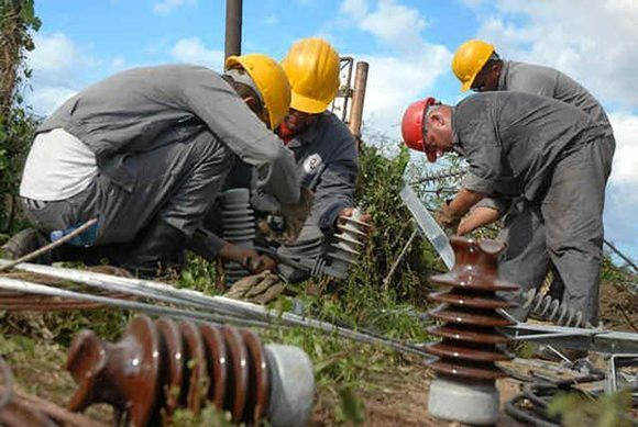 Trabajadores eléctricos de la provincia de Pinar del Río, restablecen líneas afectadas por el huracán Sandy en Nicaro, municipio de Mayarí, Holguín. AIN FOTO/Juan Pablo CARRERAS