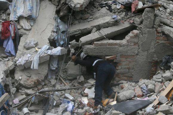 Un trabajador busca víctimas entre los escombros de un edificio derrumbado tras el terremoto. Foto: Eduardo Verdugo / AP