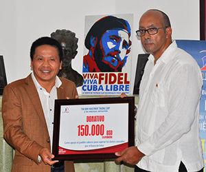 Tran Thant Tu, al entregar un cheque simbólico al embajador Herminio López Díaz. Foto: Prensa Latina.