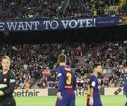 """Jugadores del Barcelona, en el estadio Camp Nou; detrás, un cartel cuelga de las gradas con la leyenda """"Queremos votar"""", en un partido de la Liga de España ante el Eibar, el 19 de septiembre de 2017. Foto: Albert Gea / Reuters."""