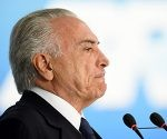 Brazilian President Michel Temer speaks during the signing ceremony of the decree that fees differential prices for payment in cash and with credit card at the Planalto Palace in Brasilia, on June 26, 2017.  Temer faces his own crisis with the prosecutor general expected to request formal corruption charges against the president Monday or Tuesday. / AFP PHOTO / EVARISTO SA