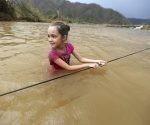 Una niña cruza un río agarrándose a una cuerda en Morovis (Puerto Rico) tras el paso del huracán. Foto: AP.