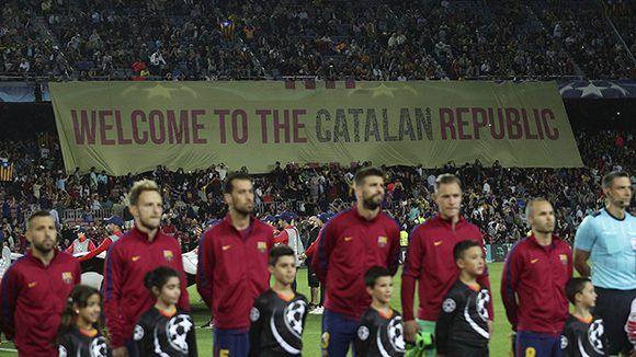 """Futbolistas del Barcelona forman para el partido ante la Juventus, de Italia, mientras los fanáticos muestran la bandera """"Bienvenidos a la República catalana"""", el 12 de septiembre de 2017. Foto: Albert Gea / Reuters"""