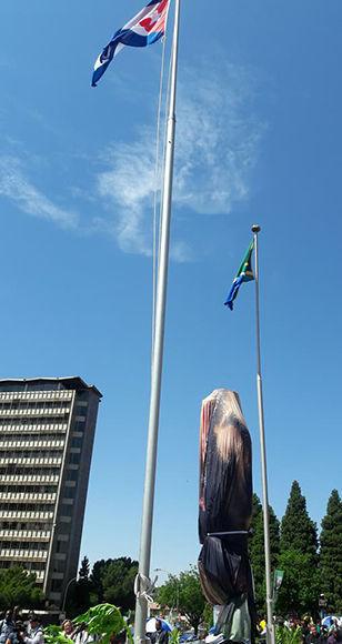 La estatua entra las banderas de Cuba y Sudáfrica, antes de ser develada. Foto: @frankfundoraacosta/ Facebook.