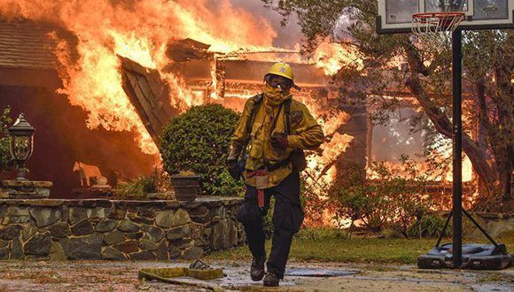 Un bombero trabaja el lunes en la extinción del incendio mientras las llamas devoran una casa en Anaheim Hills (California). Foto: Jeff Gritchen / AP