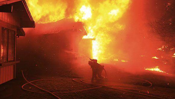 Un bombero intenta proteger una casa del fuego en Coffey Park, California. Foto: Kent Porter / AP