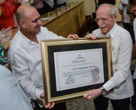 El Dr. Roberto Morales Ojeda (I), Ministro de Salud Pública de Cuba y miembro del Buró Político del Comité Central del Partido, entrega al Dr.C. Néstor Manuel Pérez Lache, el Premio al Mérito Científico por la Obra de toda La Vida, durante el acto del Premio Anual de Salud 2017. Foto: Marcelino Vázquez/ ACN.