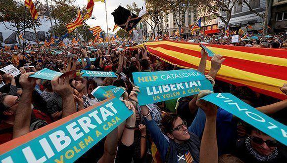 Manifestantes portan pancartas y banderas independentistas. Foto: Rafael Marchante / Reuters