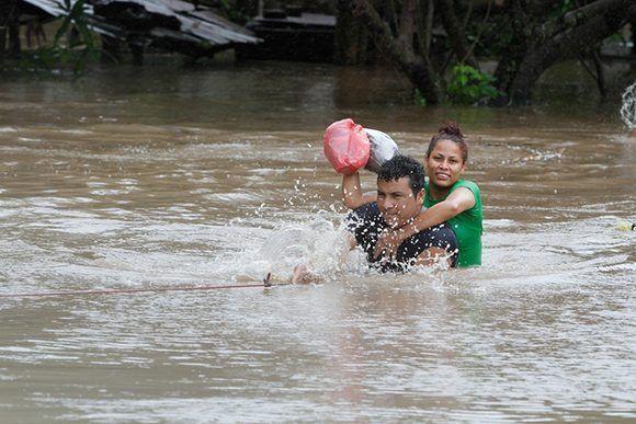 Dos personas tratan de salvarse en medio de las inundaciones en Rivas. Foto: Bismarck Picado/ El Nuevo Diario.