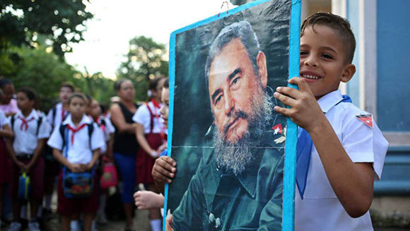 Un niño sostiene un retrato de Fidel. Foto: Alejandro Ernesto/ EFE.