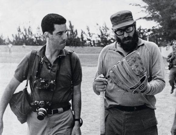Fidel se prueba un guante en un terreno de béisbol. A su lado el fotógrafo estadounidense Lee Lockwood.