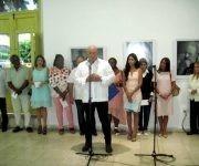 Alex Castro habla en la inauguración de su expo en Santiago. Detrás, las máximas autoridades de Santiago de Cuba, la escritora Teresa Melo y familiares del Comandante en Jefe. Foto: Miguel Ángel Gaínza