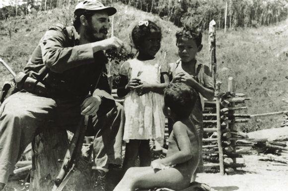 Los niños escuchan historias que narra el Comandante Fidel Castro. La niña es hija del campesino Medina, integrante del Quinteto Rebelde, 1958. Sitio Fidel Soldado de las Ideas