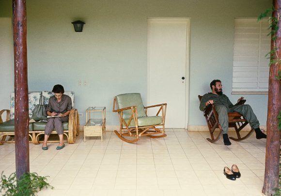 Fidel descansando en el portal de una casa en la Isla de Pinos (hoy Isla de la Juventud). En el otro extremo de la foto, Celia Sánchez hace apuntes. 1965. Foto: Lee Lockwood