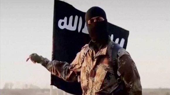 Un yihadista delante de la bandera del Estado Islámico, derrotado en Siria e Iraq. Foto: Reuters.