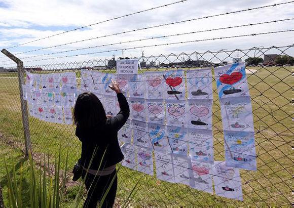 Una mujer cuelga un dibujo con mensaje de apoyo a la tripulación del submarino desaparecido. Foto: Marcos Brindicci / Reuters