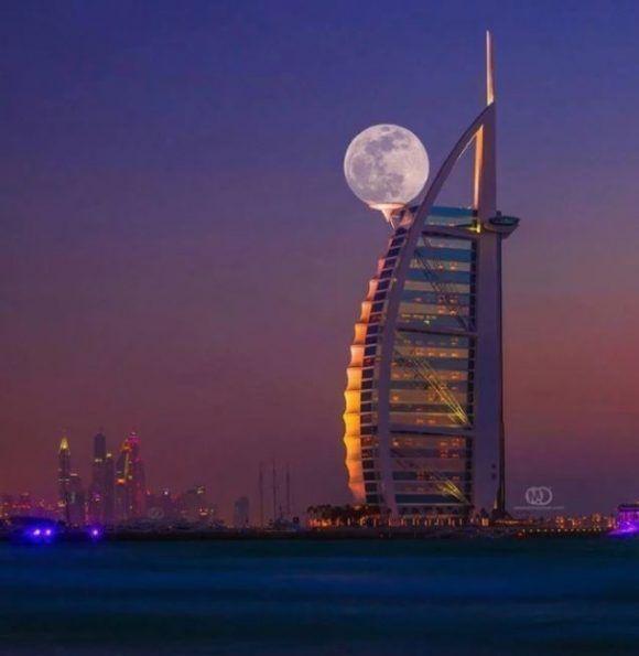 La luna se posa sobre el Burj Al Arab, en Dubai. Foto: Mo Aoun.