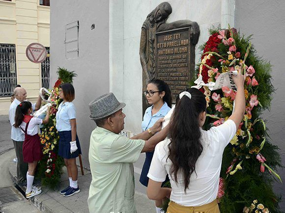 Combatientes de la lucha clandestina junto a pioneros de la escuela Secundaria Básica Roberto Rodríguez arreglan las cintas de las ofrendas florales enviadas por el General de Ejército Raúl Castro Ruz, Primer Secretario del Partido Comunista de Cuba y Presidente de los Consejos de Estado y de Ministros, y en nombre del pueblo de Cuba y de los familiares de los héroes y mártires de las acciones del 30 de noviembre de 1956, en el acto por el aniversario 61 del levantamiento armado en Santiago de Cuba. 30 de noviembre de 2017. ACN FOTO/Miguel RUBIERA JUSTIZ/sdl