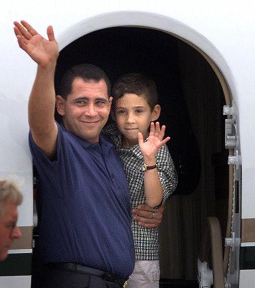 Padre e hijo suben al avión en Washington DC que los traerá de vuelta a Cuba. Foto: AFP.
