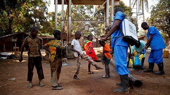 Niños con unos empleados de la Cruz Roja en Forécariah, Guinea. 30 de enero de 2015. Foto: Reuters.