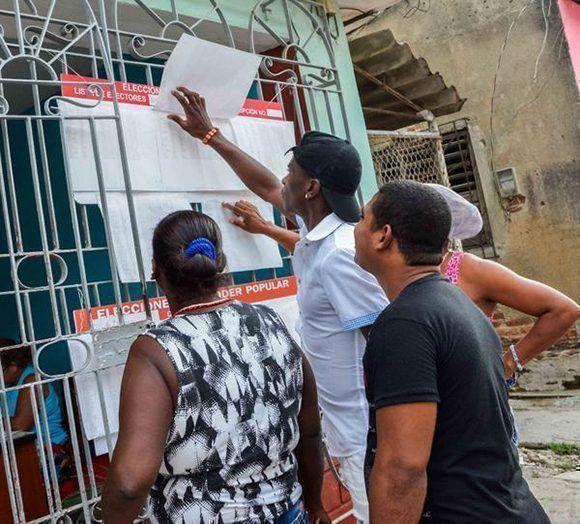 Electores tuneros observan la biografía de sus candidatos, en el comienzo de la jornada de elecciones para elegir a los delegados a las Asambleas Municipales del Poder Popular, en Las Tunas. Foto: Tomade de ACN