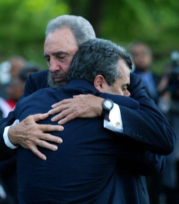 El mandatario Fidel Castro abraza a Carlos Cremata, presidente del Comité de Familiares de las Víctimas de la Voladura del Avión de Barbados, que explotó en pleno vuelo por acción terrorista, que costará la vida a 73 personas. Bridgetown, Barbados