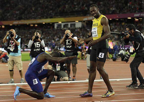 Justin Gatlin se arrodilla ante Usain Bolt luego de vencerlo en el Mundial. Foto: AP.