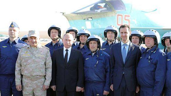 Putin y Assad posan con militares en la base aérea de Hmeimim, en Siria. Foto: Reuters.