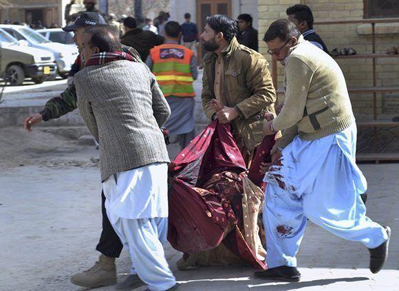 Soldados paramilitares y voluntarios trasladan a una mujer herida en el atentado. Foto: AP.